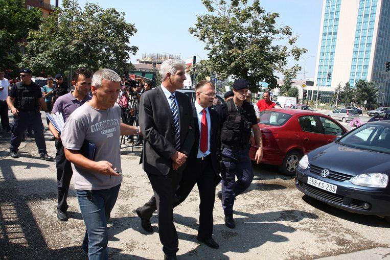 Gouverneur Hashim Rexhepi van de Centrale Bank van Kosovo (met streepjesdas) wordt door politiemensen weggevoerd. Hij wordt verdacht van grootschalige fraude (Reuters) Beeld REUTERS