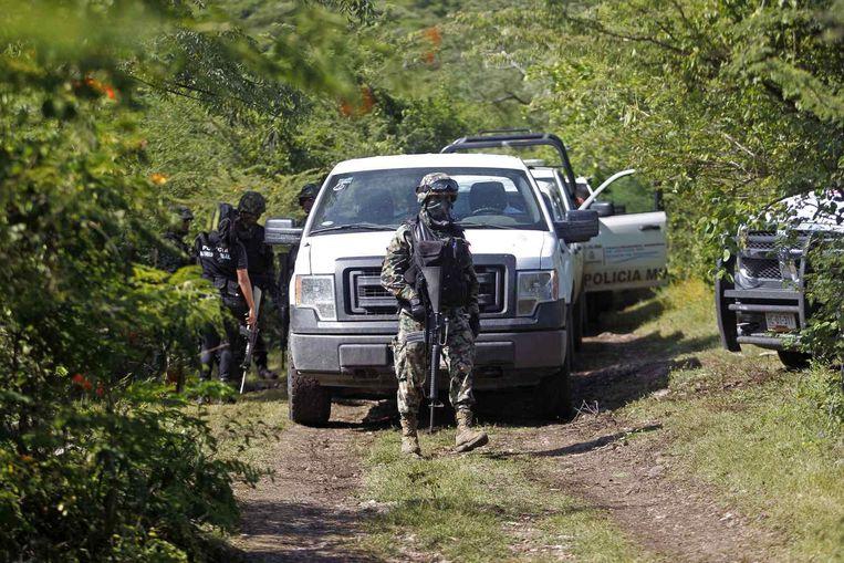 Militairen bij de plaats van het massagraf. Beeld reuters