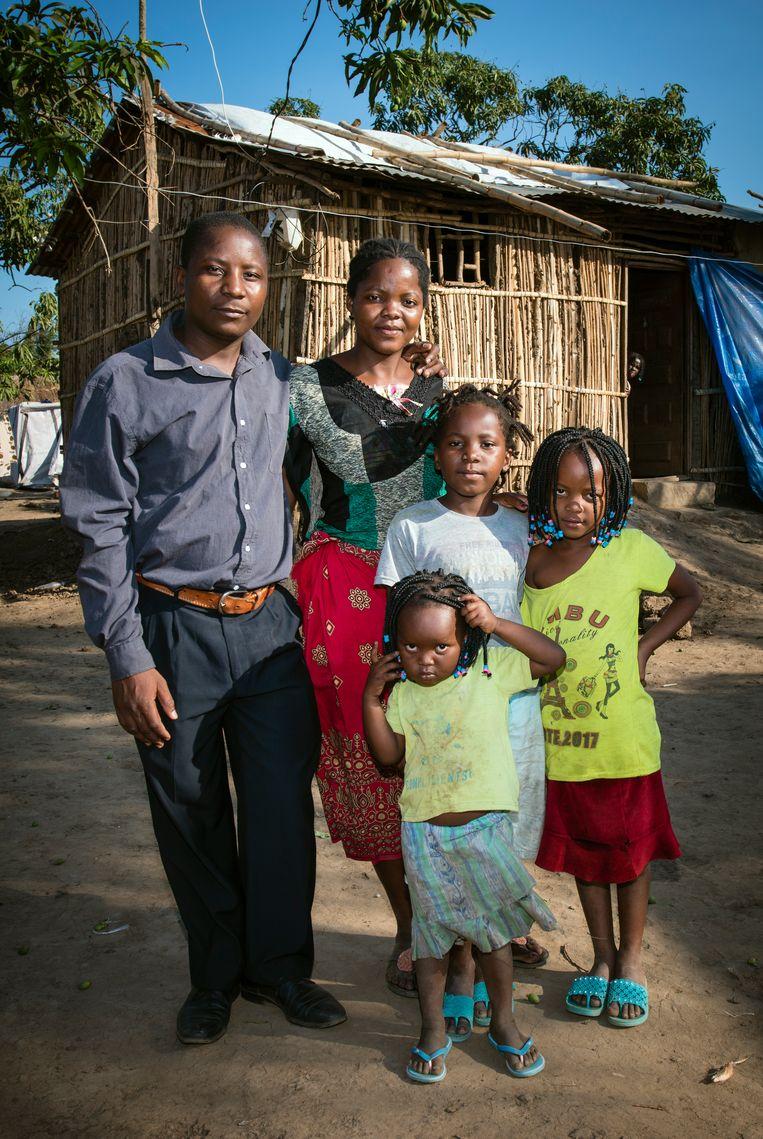 Raposo Rego met zijn vrouw Maria en drie dochters Fatima (grijs shirt), Luisa (rechts) en Rosita voor zijn huis in Buzi. Beeld Bram Lammers