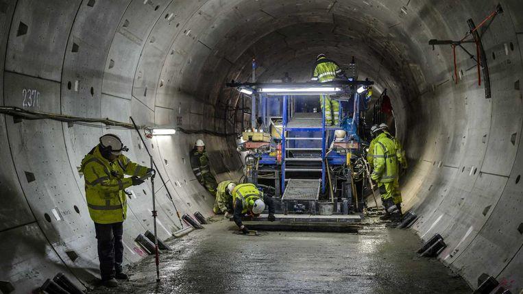 Werknemers maken met een enorme pavermachine een vlakke bodem in de ronde tunnels van de Noord-Zuidlijn. Hierop kan het metrospoor worden aangelegd. Beeld anp