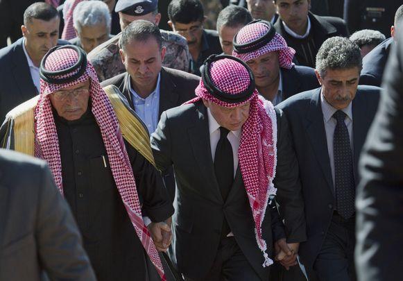 Koning Abdullah II, midden, naast de vader van de geëxecuteerde piloot Muaht al-Kaseasbeh (links), vandaag tijdens een herdenkingsplechtigheid.