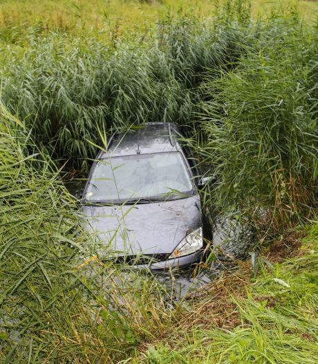 Verlaten auto in het water aan de Middelweg in Dordrecht