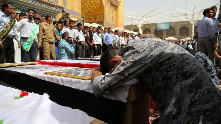 Een Iraakse man rouwt bij de kisten van Iraakse soldaten die omkwamen bij een zelfmoordaanslag door IS-strijders.