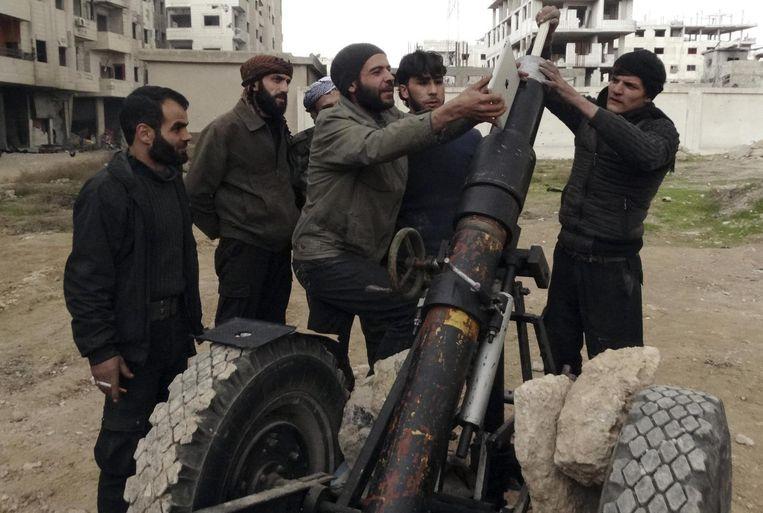 Strijders van het Vrije Syrische Leger gebruiken een Ipad bij het richten van hun wapen in een buitenwijk van de hoofdstad Damascus. Beeld Msallam Abd Albaset / Reuters