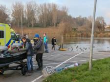 Vissers redden omgeslagen kanoër uit het water