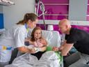 Verpleegkundige Laura legt Faye in de armen van moeder Fabienne. Papa kijkt toe.