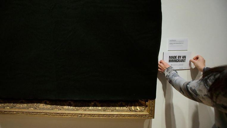 Een medewerker van het Davis Museum bedekt een kunstwerk dat gemaakt is of gedoneerd door immigranten. Beeld ap