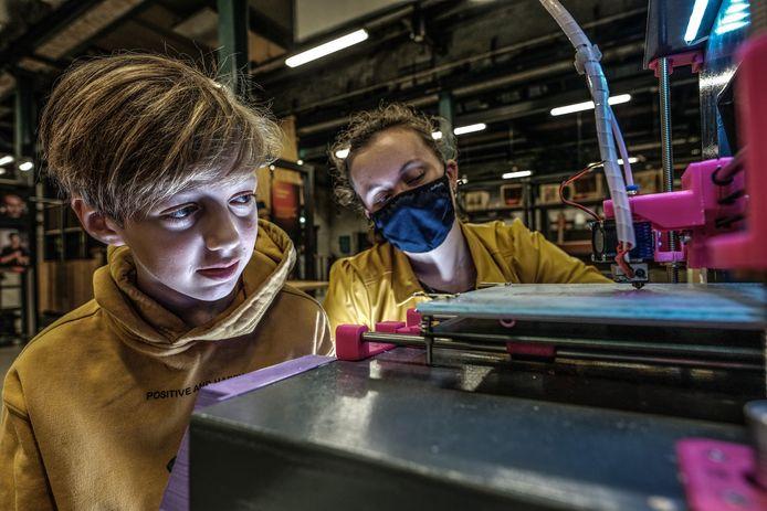 Elien Ratering (met mondkapje) en Luca Bruijn druk in de weer met de 3D-printer die Luca heeft gemaakt. Foto Jan van den Brink.