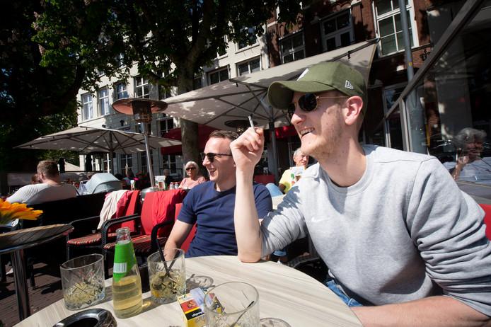 Max Vlaswinkel (met pet) geniet van een sigaret op het terras van Goesting aan de Brink. Kameraad Peter-Maarten Pieper rookt niet. Hij zegt geen last van Max' gepaf te hebben.