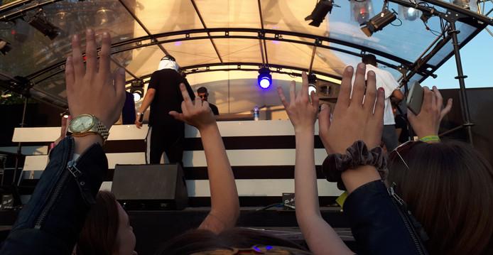 Typerend beeld bij het optreden van YouTube-act Supergaande: artiesten Nesim Najih en Qucee kijken niet naar het publiek maar naar de camera achterop het podium.