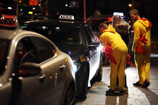 Leutgangers die een taxi scoren.