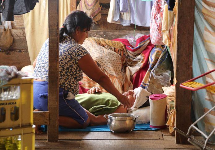 Een familielid verzorgt een zieke man in Iquitos, Peru. Beide dragen geen mondkapjes.