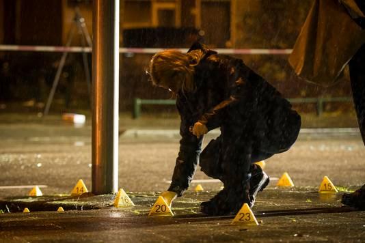 De recherche doet onderzoek naar de kogelhulzen op de grond