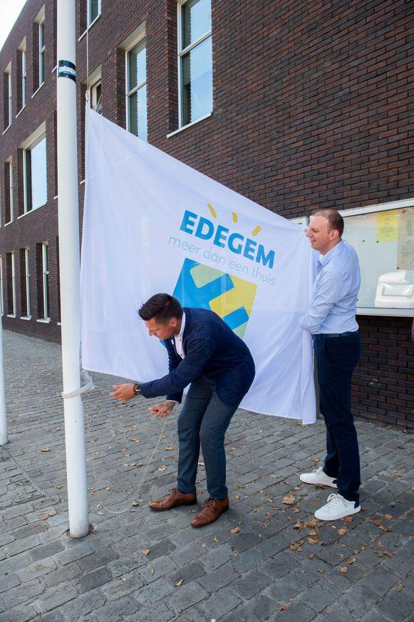 De burgemeester en schepen Vancraeyenest hijsen de nieuwe vlag van Edegem.