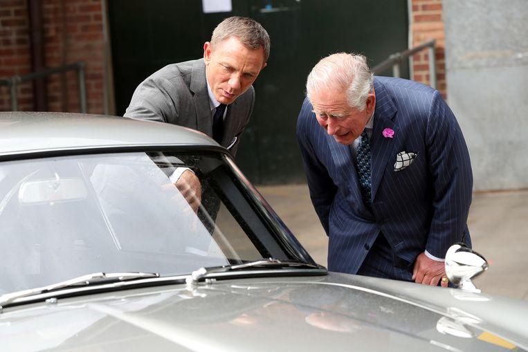 Prins Charles en Daniel Craig bestuderen de auto's op de set.
