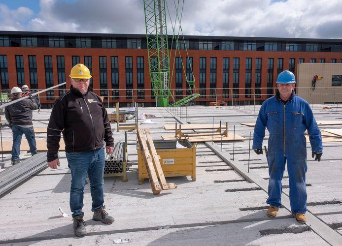 Uitvoerder Jan Marinissen (l) en ijzervlechter Peter van Rijswijk houden op de bouwplaats bij het Van der Valk hotel in Middelburg anderhalve meter afstand.