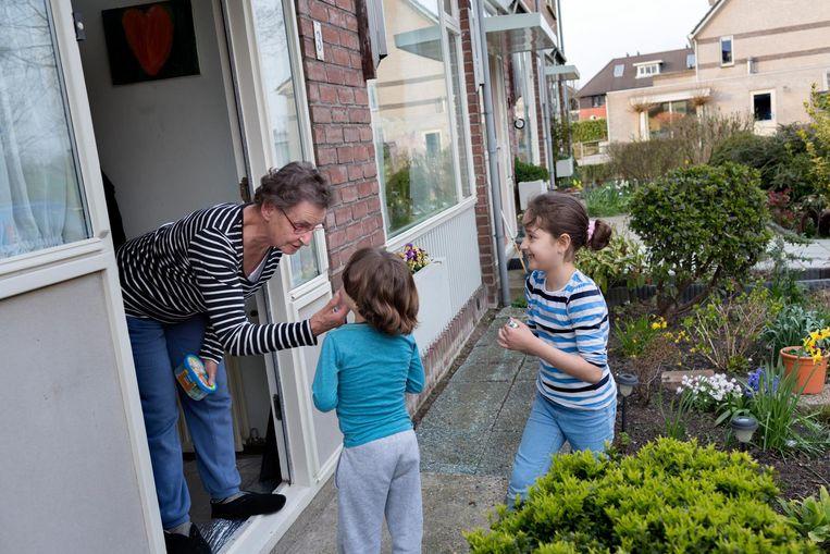 Dochter Leian en zoon Mahmoud brengen de buurvrouw een door vader Aiman gebakken hamburger met frietjes. Beeld Inge van Mill
