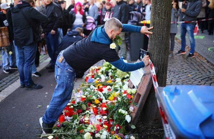 Een man legt bloemen neer op de plek waar de schutter gisteren een inwoner van Halle doodschoot.