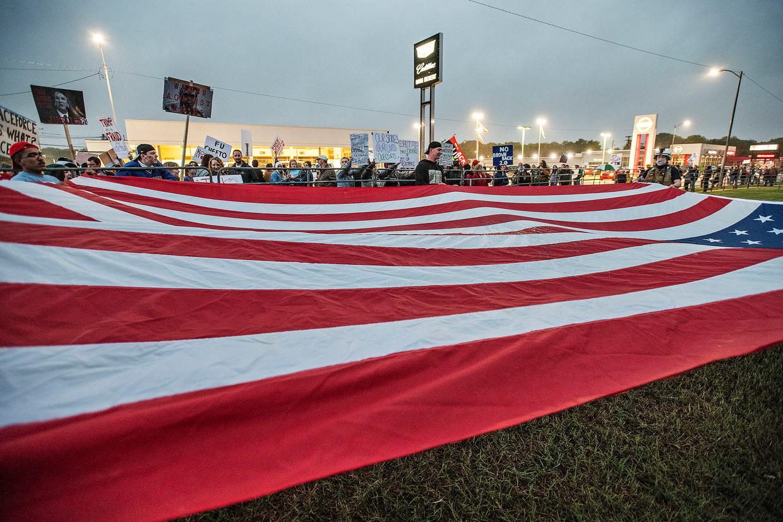 Aanhangers van Trump ontvouwen een enorme Amerikaanse vlag.