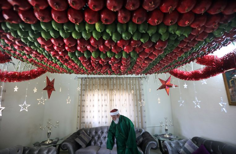 Een lid van de Samaritaanse gemeenschap in Nablus op de westelijke Jordaanoever loopt onder een plafond dat is versierd met vruchten die horen bij de Soekot, het Loofhuttenfeest dat dit weekend begint. Daarmee wordt de uittocht van de Israëlieten uit Egypte en hun veertigjarige zwerftocht in de Sinaï-woestijn herdacht. Beeld EPA