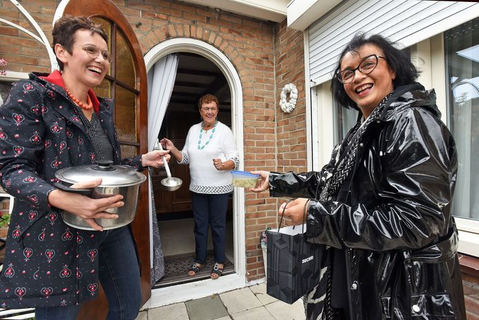 Katrien Kerckaert (l) en Corine de Serière du Bizournet (r) brengen soep aan de deur bij Tilly Goossen.