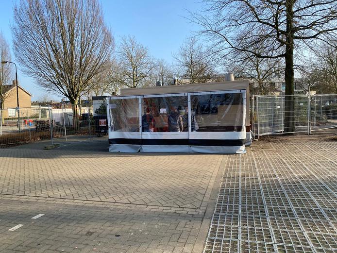De tijdelijke frietkraam in Den Dungen met daarachter snackbar 't Pleintje, omringd door hekken.