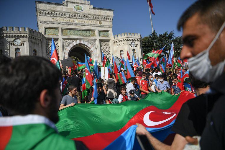 Demonstranten dragen de nationale Azerbeidzjaanse vlag tijdens een protest in Istanbul op 4 oktober. Turkije verbergt zijn enthousiaste steun voor het Azerbeidzjaanse militaire offensief niet. Beeld AFP