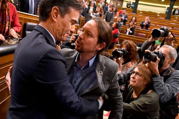 Blijdschap bij Pedro Sanchez (links) van PSOE en Unidas Podemos-leider Pablo Iglesias nadat dinsdag bekend is geworden dat ze een coalitie kunnen vormen. Beeld AFP