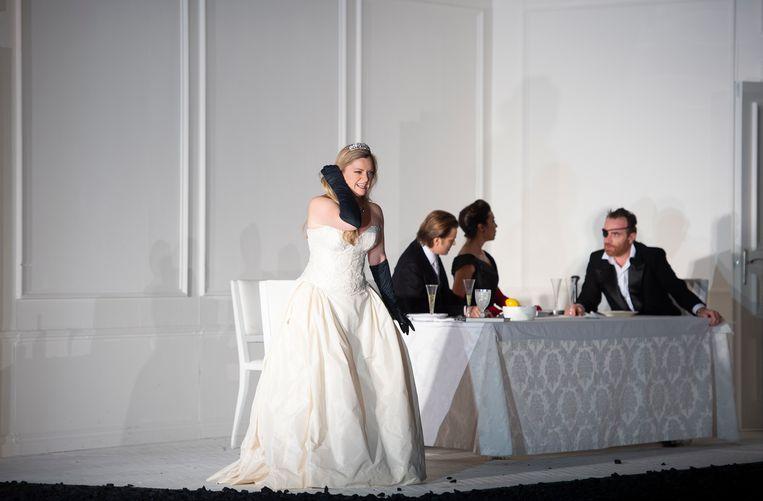 Rond de gedekte tafel in de witte villa spelen zich diverse scènes af.  Beeld DNO