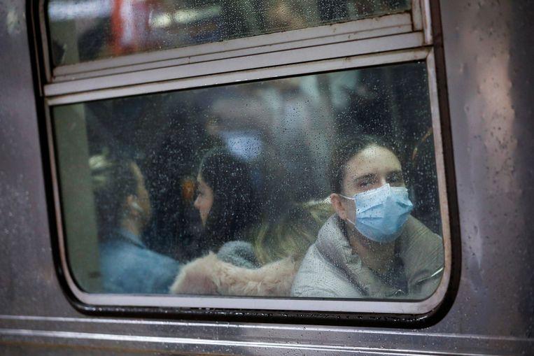 Een vrouw in de New Yorkse metro draagt een gezichtsmaskertje vanwege de corona-uitbraak.  Beeld Andrew Kelly / Reuters