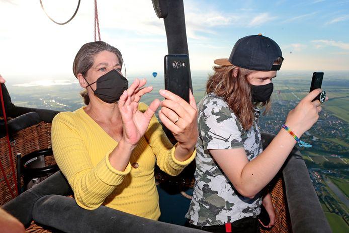 Marja en Lisanne Borst druk met foto's maken tijdens hun ballonvlucht boven het Groene Hart.