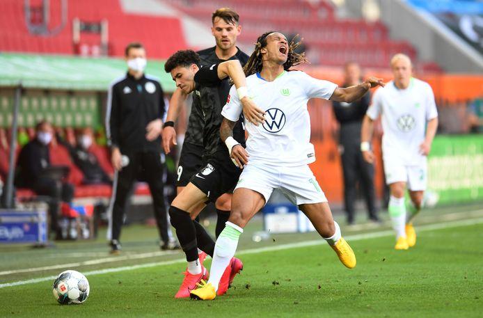 Ruben Vargas van Augsburg stopt Wolfsburg-speler Kevin Mbabu af.