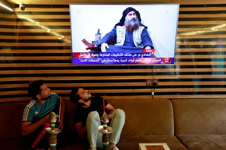 Irakese jongeren kijken in de stad Najaf naar het nieuws van de dood van al-Baghdadi.  Beeld Reuters