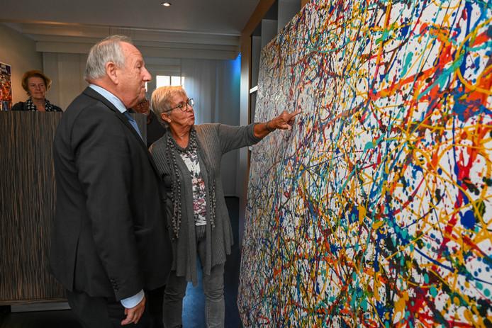 Gerard van den Tweel en docent Rolina van Vliet bij het schilderij.