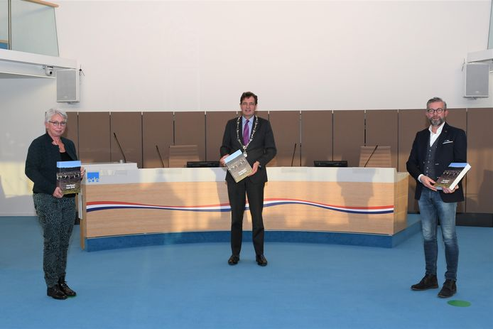 Auteur Peter van Beek (rechts) overhandigt het boek aan burgemeester René Verhulst (midden). Bij de presentatie was ook bijzonder hoogleraar Gelderse Geschiedenis, Dolly Verhoeven aanwezig