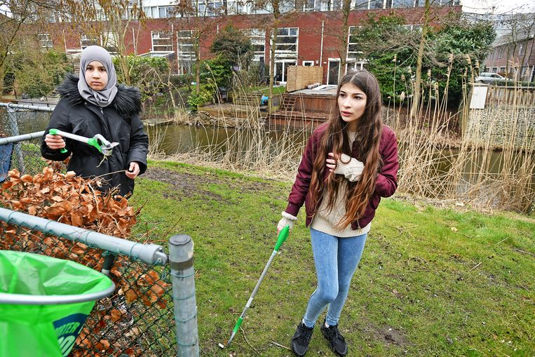 Leerling van het Amsterdamse Wellantcollege ruimen in hun wijk zwerfvuil op. Foto Guus Dubbelman / de Volkskrant Beeld