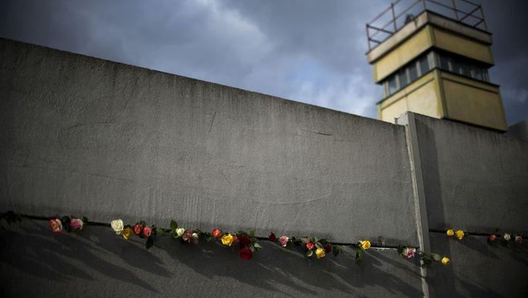Rozen bij de Berlijnse Muur om de slachtoffers te herdenken. Beeld afp