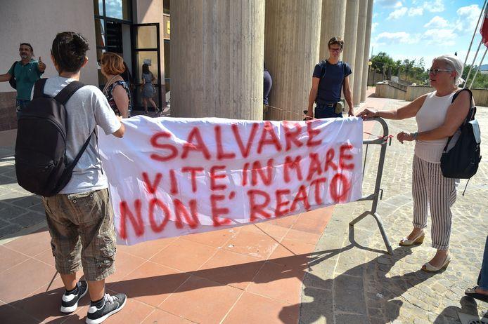 """Rackete verscheen maandag voor de rechter in het Sicilaanse Agrigento. """"Levens redden op zee is geen misdaad"""", luidde het opschrift op dit spandoek."""