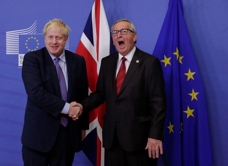 Britse premier Boris Johnson (l) en president van de Europese Commissie Jean-Claude Juncker (r) schudden elkaar de hand tijdens een persconferentie over de Brexit-deal in Brussel.  Beeld EPA