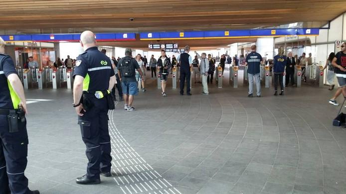 NS-medewerkers leggen reizigers uit dat ze maandag op Arnhem CS moeten inchecken voor ze het station in mogen.