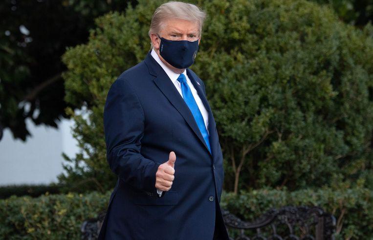 Trump kan het nog opbrengen een duim in de lucht te steken op weg naar de helikopter die hem naar het Walter Reed Military Medical Center zal brengen. Beeld AFP