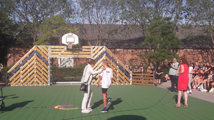 Feest op het Zwijsen College in Veghel: het nieuwe schoolplein is officieel geopend. De wethouder en een leerling gaan de basket uitproberen.