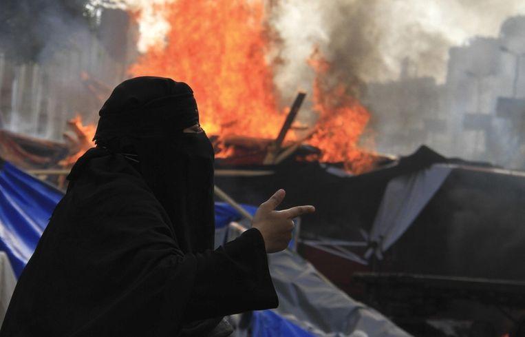 Een lid van de Moslim Broederschap bij de brandende tenten van een protestkamp. Beeld reuters