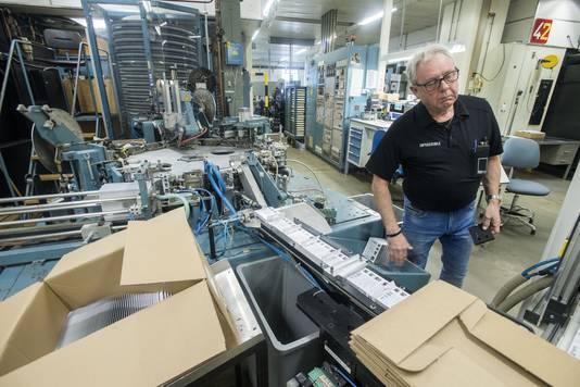 Johan Brouwer bij de verpakkinglijn van een filmproductiemachine