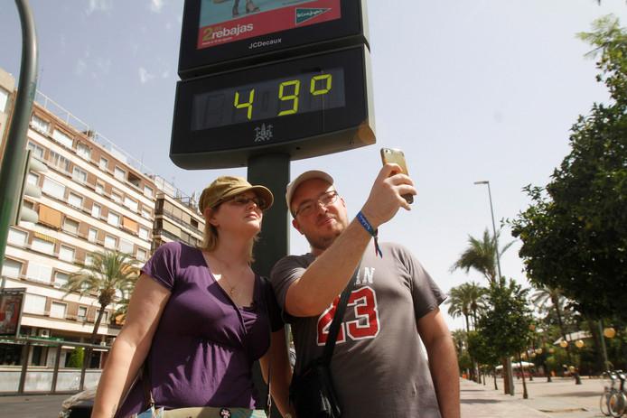 Toeristen maken een selfie bij een reclamebord dat de temperatuur weergeeft in Cordoba.