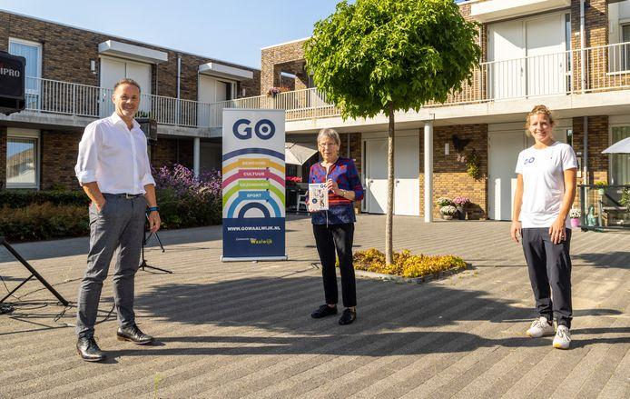 Mevrouw Smolders krijgt het eerste exemplaar van de Go Fit beweeggids van wethouder John van den Hoven en beweegcoach Annika Jabroer.