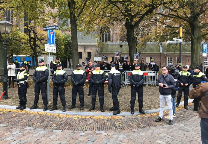 Politieagenten vormen een buffer voor het protestvak van Kick Out Zwarte Piet in Dordrecht.