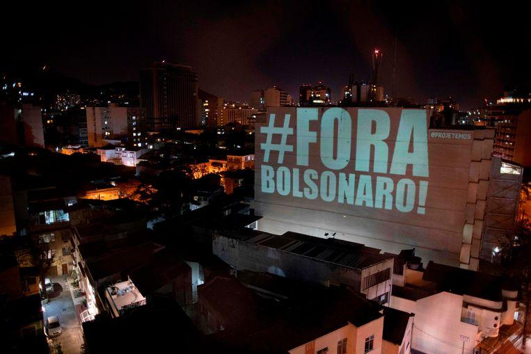 In de Braziliaanse stad Rio de Janeiro wordt op een gebouw de tekst 'weg met Bolsonaro' geprojecteerd. Brazilië is de grens van 100 duizend coronadoden gepasseerd.  Beeld AFP