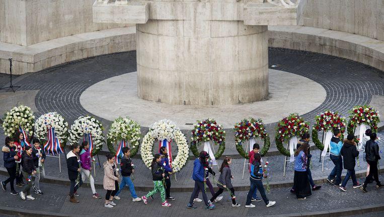 Schoolkinderen lopen langs de kransen bij het Monument op de Dam tijdens de Nationale Dodenherdenking. Beeld anp