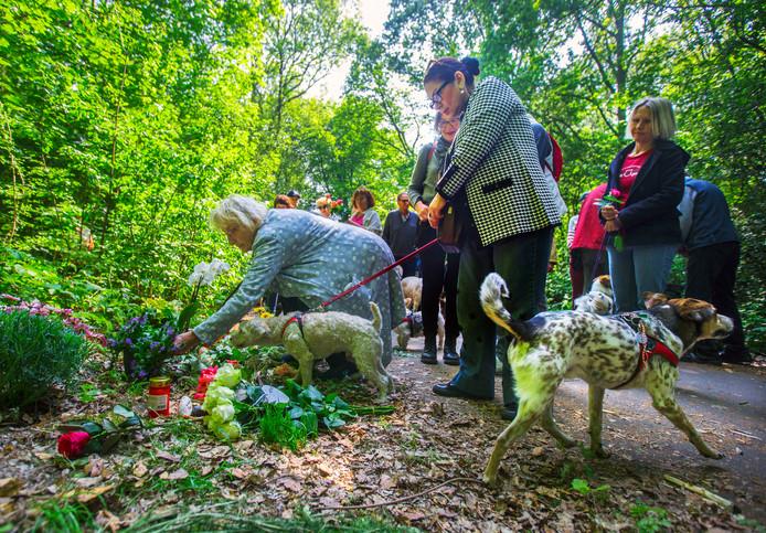 Deelnemers van de stille tocht leggen bloemen neer als eerbetoon aan Etsuko, de vrouw die op 4 mei in de Scheveningse Bosjes om het leven werd gebracht.